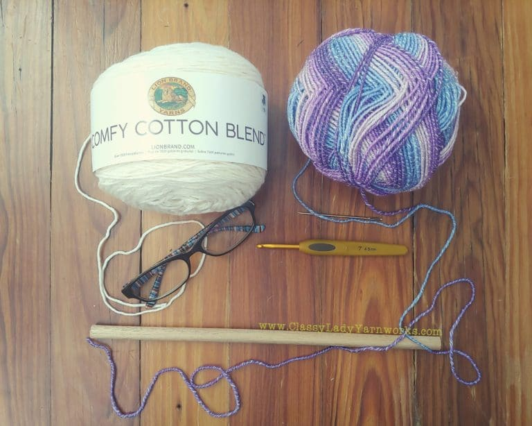 Image of various crochet notions and yarn. Lion brand comfy cotton in whipped cream, lion brand ice cream cotton blend in grape, clover 4.5mm hook, yarn needle, reading glasses and wooden dowel rod. All things used in the Shit. wall art crochet pattern.